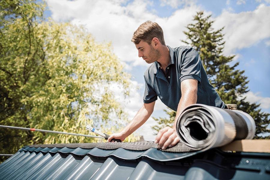 Dachdecker bei der Abdichtung eines Steildachs mit Firstrolle